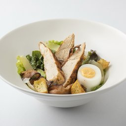 Caesar salad with herb croutons, grilled chicken pieces, roasted bacon and egg