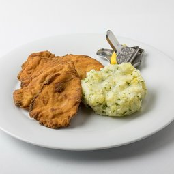Fried chicken or pork schnitzel with mashed potatoes and lemon