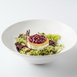 Assortment of shredded lettuce leaves with pomegranate, grilled goat cheese and cranberries