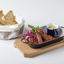 Smoked sausages roasted with dark beer and vegetables, served with tarragon mustard and bread from our oven